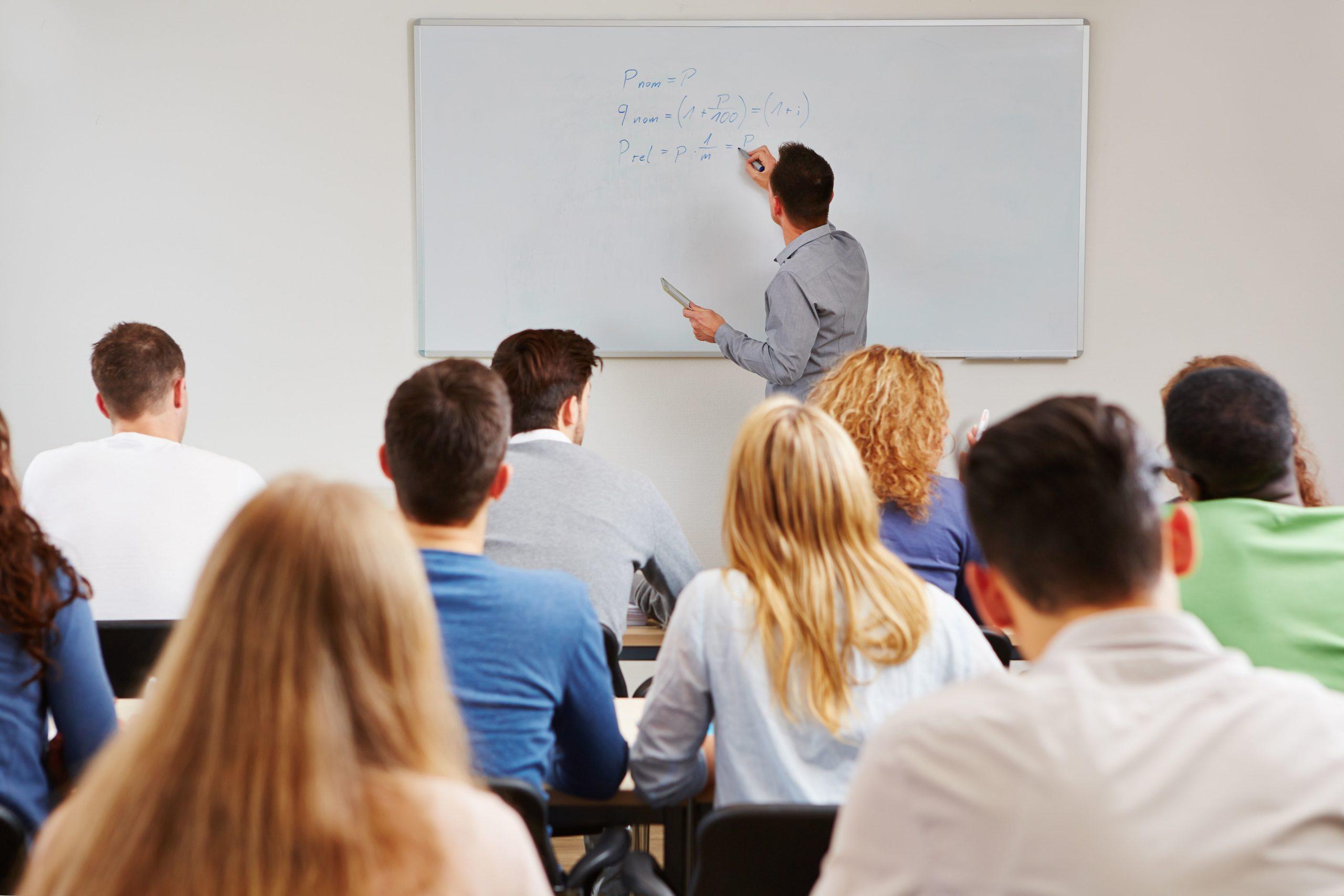Professeur écrivant au tableau devant une classe
