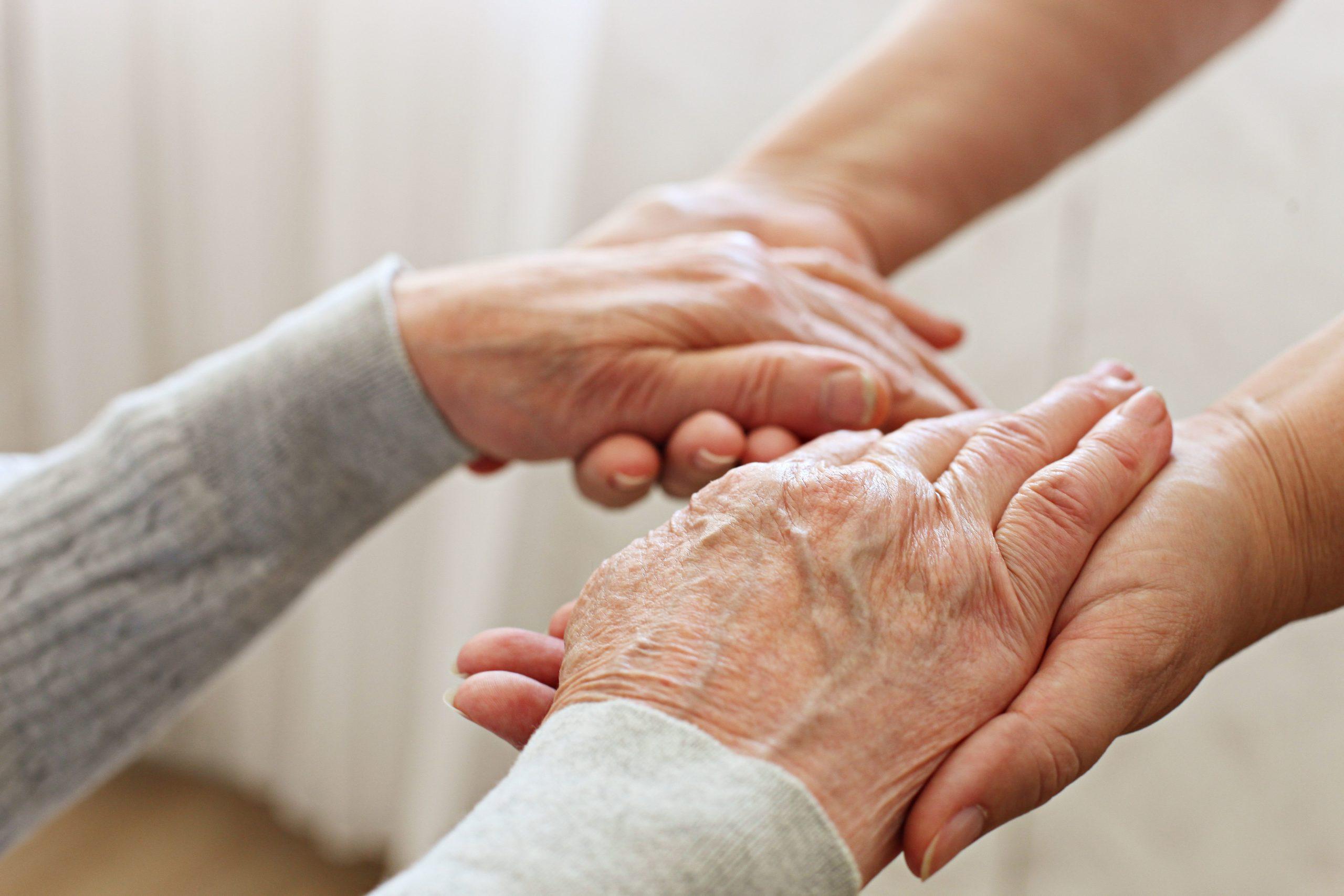 Mains qui tiennent des mains de personne agée
